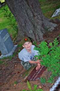 AK Kid investigates a headstone at the Sitka National Memorial Cemetery.